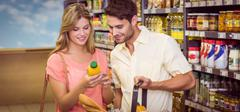 Smiling bright couple buying food products with shopping basket Stock Photos