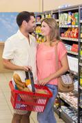 Smiling bright couple buying food products using shopping basket - stock photo