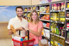 Portrait of smiling bright couple buying food products using shopping basket - stock photo