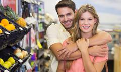 Portrait of smiling bright couple buying food products arm around - stock photo