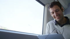 4k Casual man on train journey with computer tablet and earphones - stock footage