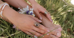 Girl's feet in grass with fresh flowers and gold jewellery Stock Footage