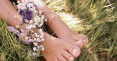 Girl's feet in green grass with flowers and foot jewellery - stock footage