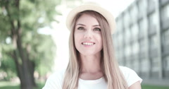 Portrait of pretty cheerful woman wearing hat in sunny warm weather day. Walking Stock Footage