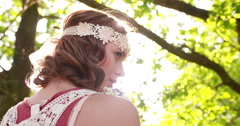 Boho girl surrounded by leaves in a summer park Stock Footage