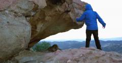 4k girl climbing up a rock to a cave  in desert mountains at sunset Stock Footage