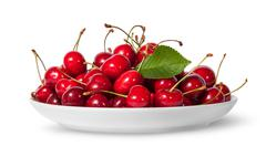 Pile of sweet cherries with leaf on white plate - stock photo