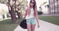 Sam 7583 student walking with the bag and sunglasses near campus Stock Footage