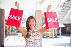 Portrait of euphoric woman holding two sale shopping bags - stock photo