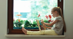 Girl learning to count with abacus and sitting on the sill Stock Footage