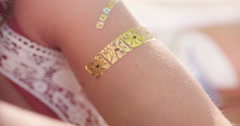 Boho girl with a gold foil temporary arm tattoo - stock footage