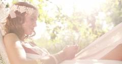 Boho girl lying in a summer hammock using her phone Stock Footage