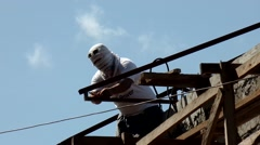 Welder on rooftop joining trusses Stock Footage