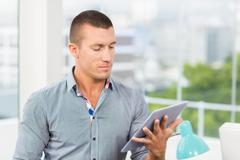 Attentive businessman watching at his tablet Stock Photos