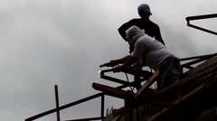 Welder on rooftop joining trusses Time lapse Stock Footage