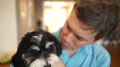 Man holds pets and kisses dog Stock Footage