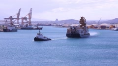 HONOLULU, HAWAII - JULY 2015: Tug boat pulls heavily loaded barge in Honolulu Stock Footage