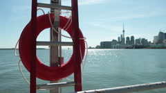 Red lifesaver in foreground of city skyline - stock footage