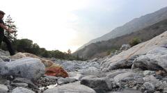 Man gazes at rocky mountain stream Stock Footage