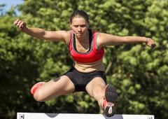 Young woman 20 years hurdling - stock photo