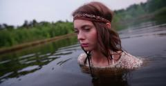 Girl in vintage white lace dress standing in a lake - stock footage