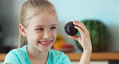 Girl eating plums. Child promotes fruit plums Stock Footage