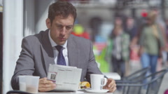 4k Businessman reading newspaper and having lunch at outdoor city cafe Stock Footage