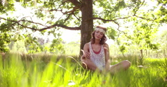 Hippie girl sitting in lush grass in a summer park Stock Footage