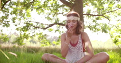 Hippie girl smelling a flower in a summer park - stock footage