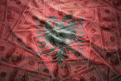 colorful waving albanian flag on a american dollar money background - stock photo