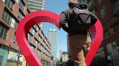 Man Walking Through Heart-shaped Archway Stock Footage