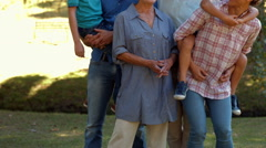 Happy family smiling at the camera in the park - stock footage