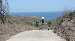 Drone filming a biker walking on a dirt road Stock Footage
