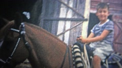 1953: Children from the big city sitting on horses for the first time. Stock Footage