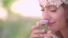 Girl in boho style smelling a fresh flower in nature - stock footage