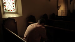 Man prays in church pew Stock Footage