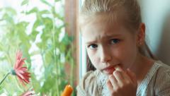 Child has a toothache. Girl eating carrot - stock footage