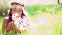 Smiling hippie girl lying in grass holding wild flowers - stock footage