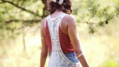 Girl in white dress walking in sunlit summer park Stock Footage