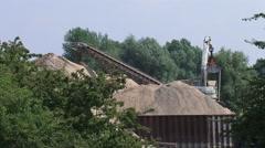 Grabbing crane unloads a sand barge - medium shot Stock Footage