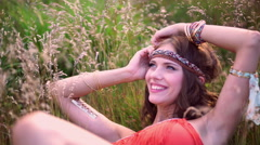 Boho girl smiling lying in a field of wild grass - stock footage