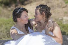 Two brides smile and embrace in nature surroundings Stock Photos