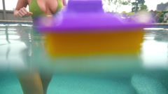 Woman picks up a toy boat floating in a pool - stock footage
