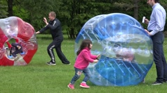 Father push fast his son child in red zorb ball on meadow. 4K Stock Footage