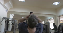 Men doing situps and bench press exercises Stock Footage