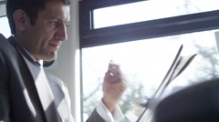 4k businessman disappointed with results he reads in newspaper on commuter train Stock Footage
