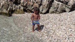 Small child plays with a box at the seaside Stock Footage