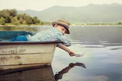 Little boy launch paper ship lying in old boat Stock Photos