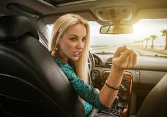 Attractive blonde female emotional talks to rear seat passenger Stock Photos