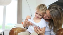 Mommy with little girl playing with video game player Stock Footage